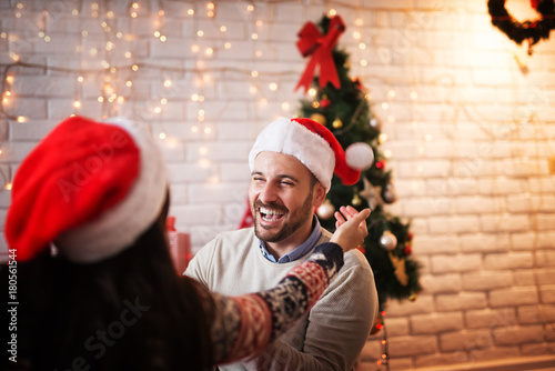 85ef1dd0696 Rear view of girl with Santa hat wants to hug her handsome bearded young  boyfriend for Christmas holidays at home.
