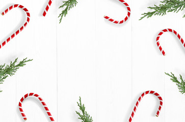 Christmas styled stock photo. White wooden background with candy cane decorations, evergreen juniperus branches and empty space. Top view. Festive composition.