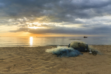 Fishing nets are placed on the beach, while the sun is rising from the horizon
