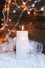 Two burning candles with a deer with christmas decorative balls on snow and Christmas lights. Christmas decorations on wooden background.