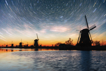 Colorful spring night with traditional Dutch windmills canal in Rotterdam. Wooden pier near the lake shore. Holland. Netherlands. Fantastic starry sky and the milky way.