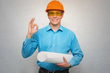 Young happy engineer worker in a helmet holding in one hand project drawings and showing OK gesture sign with his another hand isolated. Construction.