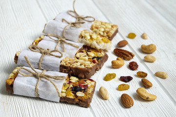 Healthy granola bars with nuts, seeds and dried fruits on the gray texture table, with copy space.