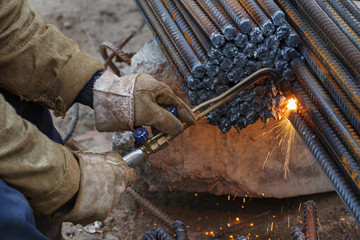 Gas cutting of metal fittings. Working gloves. Sparks.