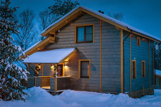 Winter evening. Snow-covered cottage. Wooden two-storey house. Cottage in winter.