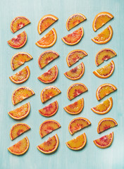 Natural fruit pattern concept. Fresh juicy blood orange slices placed in rows over light blue painted table background, top view