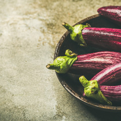 Fresh raw Fall harvest purple eggplants or aubergines in wooden bowl over grey concrete stone background, selective focus, copy space, square crop. Healthy Autumn vegan cooking ingredient