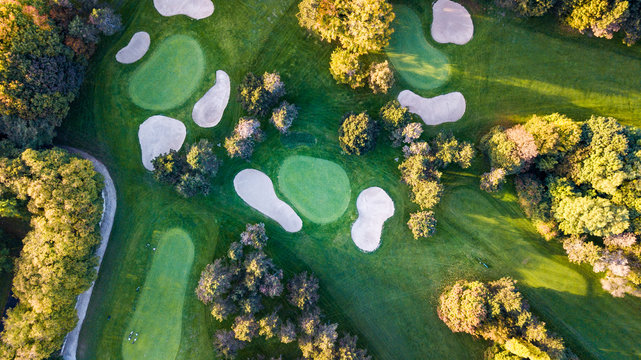 Drone view of a golf field with colorful trees