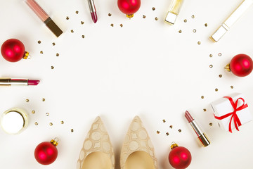Make up products with Christmas decoration and golden womans shoes on white background with copy space flat lay