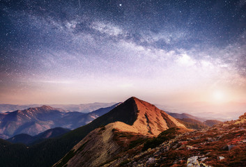 Fantastic landscape in the mountains of Ukraine. Vibrant night sky with stars and nebula and galaxy.