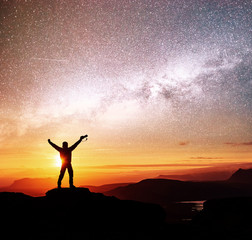Silhouette of woman is standing on top of mountain and pointing to The milky way before sunrise and enjoying with colorful night sky