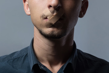 man with mouth covered by patch to forbidden him the free speeching
