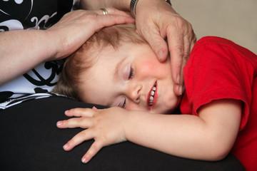 Geborgenheit: Frau Oma beschützt schlafendes Baby mit ihren Händen