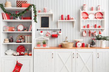 Interior light grey kitchen and red christmas decor. Preparing lunch at home on the kitchen concept.