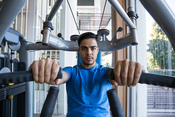 Handsome man in blue T-shirt doing exercises on exercise machine.