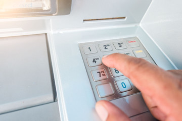 closeup ATM machine and finger hand entering pressing password for withdrawing money banknotes.