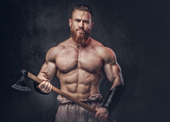 A man holds axe over dark grey background.