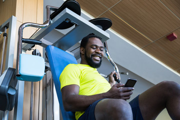 Bearded African-American man in yellow T-shirt sitting on exercise machine, using his smartphone and smiling.