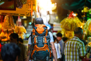 Backpacker man walking in the street of a market in a city of asia