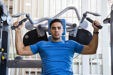 Attractive young man in blue T-shirt doing exercises on exercise machine and looking at camera.