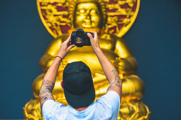 Man holding a camera and take a photo of a golden buddha