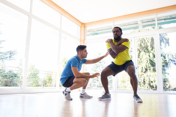 African-American man squatting in gym while his trainer helps him.