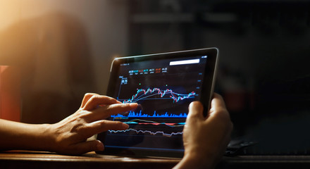 Businessman checking stock market data on tablet at night background