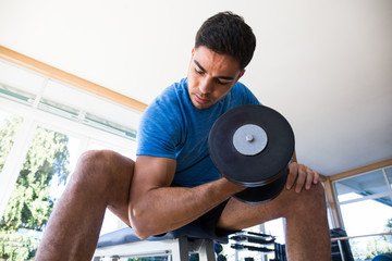 Man in sportswear sitting on bench in gym and lifting dumbbell.