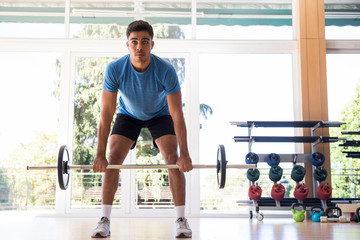 Man in blue T-shirt lifting heavy barbell during his training in gym.