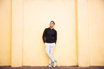 Handsome young man insportswear standing near beige wall and cheerfully smiling.