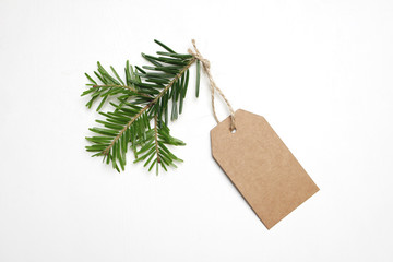 Close-up of craft paper gift tag with rope and green fir branch isolated on white background. Christmas composition, top view.