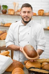 Handsome young cheerful baker offering a loaf of dark freshly baked tasty bread posing at his bakery store positivity friendly confidence salesperson assortment businessman food retail.