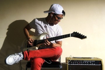 Teen playing an electric guitar