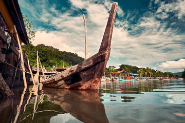 The fishing boats park with old rural wooden boat on foreground. Traditional colorful asian fishing boats in fishing village. Langkawi island, Malaysia.