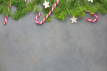 Red-white candy canes on the gray concrete background with Christmas tree. Beautiful Christmas background. Flat lay, top view