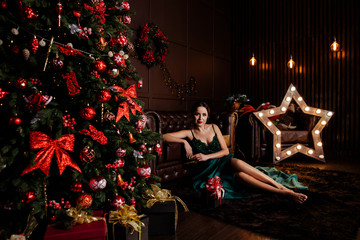 The room decorated by Christmas.  Elegant lady in green dress over christmas tree lights background.