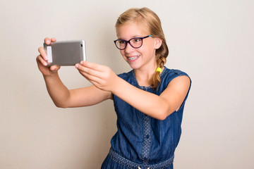 Pretty smiling teen girl in glasses making selfie photo on smartphone over white background.