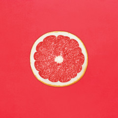 Grapefruit in flat lay Half of ripe grapefruit is lying on red background Top view Modern bright flat lay photo mockup with space for text