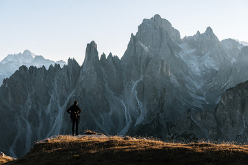 Young adult male standing and taking in the view in front of the dolomites mountains in italy