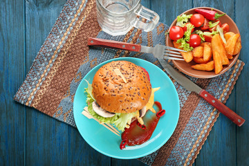 Plate with fresh tasty burger on table