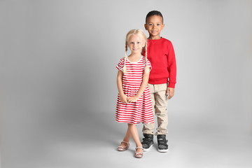 Cute fashionable children on grey background