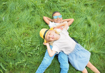Cute fashionable children lying on green lawn outdoors