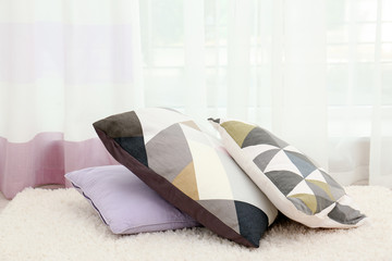 Colorful pillows on floor indoors