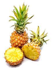 One whole pineapple and its sliced halves isolated on white background.