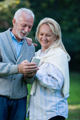 Happy senior couple using a phone, outdoors