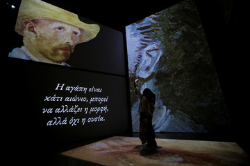 "A visitor takes a photo in front of a projection of a Vincent Van Gogh painting at the ""Van Gogh Alive"" exhibition in Athens"