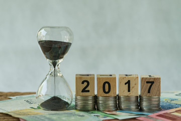 Year end 2017 business time countdown as hourglass or sandglass on pile of Euro banknotes with wooden cube block number 2017 on stack of coins