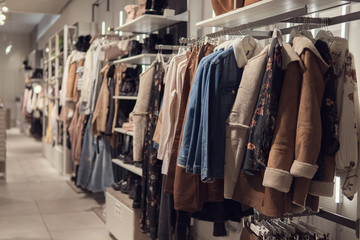 women's dresses and jacket on hangers in a retail shop.