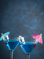 Blue cocktail drink in martini glass with umbrella and cherry
