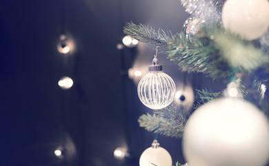 Closeup of silver bauble hanging from a decorated Christmas tree with bokeh, copy space. Xmas holiday background.